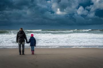 Mutter und Tochter blicken Hand in Hand aufs weite Meer