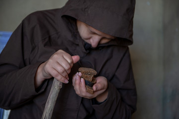 girl in dark cape holds roll and black bread in her hands. woman rehearses role of beggar woman for  amateur performance.