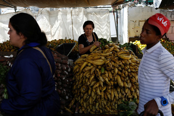 A woman selects plantains at a vegetable and fruit stall at a street market in Caracas
