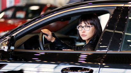 A brunette woman with eyeglasses is looking out of a car window