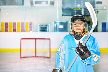 Happy girl in hockey uniform posing with stick