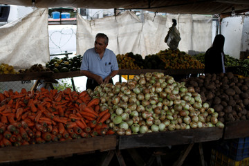 A man shops at a vegetable and fruit stall at a street market in Caracas