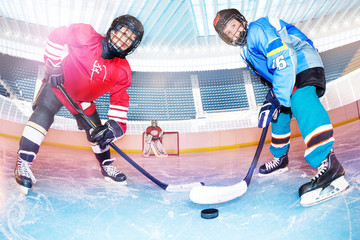 Hockey players challenging for puck on ice rink