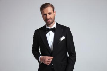 smiling elegant man holding his tuxedo's button