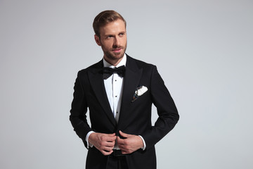 smiling elegant man buttoning his tuxedo and looks to side