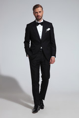 young elegant groom stepping forward with hand in pocket