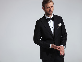 young elegant man in tuxedo holding palms together