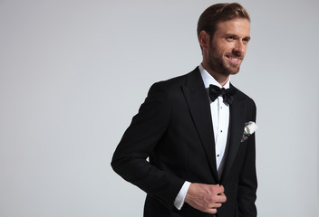Young elegant man in tuxedo holding button and laughs