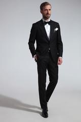 elegant man in tuxedo standing with hand in pocket