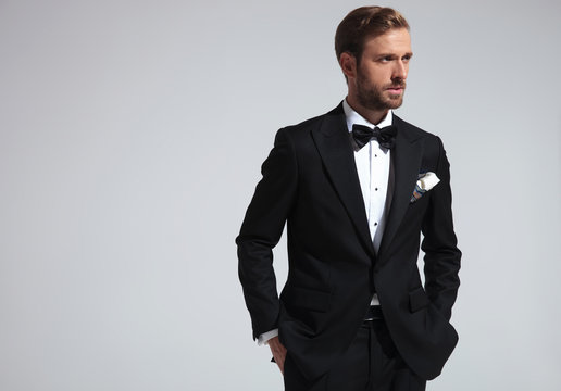 serious  man wearing tuxedo and standing with hands in pockets