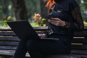 Woman using laptop and smartphone on bench