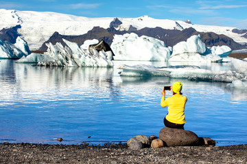 A young woman photographs on a smartphone a beautiful landscape. Woman on the background of beautiful mountains and ice