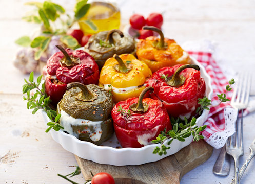 Roasted bell pepper with mushroom, rice, cheese and herbs filling in a baking dish on a white wooden table. A healthy and delicious vegetarian food.