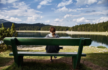 A young girl sitting on a bench. Black lake. Durmitor national Park. Montenegro.