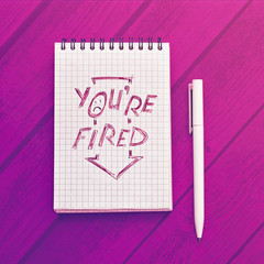 "Notepad with text in red ""You're fired"" is on a wooden background. Nearby is a white pen. Concept on the topic of dismissal, unemployed, crisis"
