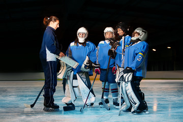 Female coach reviewing game plan with hockey team