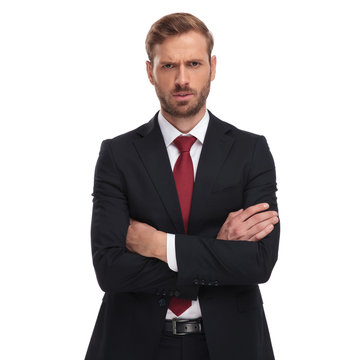 portrait of angry businessman with folded arms standing