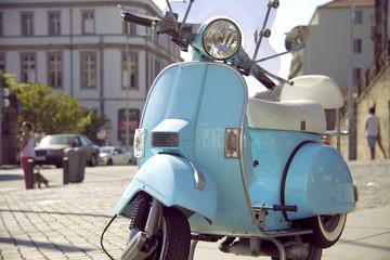 Fotorolgordijn Scooter Bonito scooter clásico de color azul claro aparcado en la acera de la calle de una gran ciudad