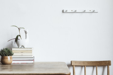 The white interior with copy space, books, vintage accessories and lama pot. Minimalistic concept of home interior.