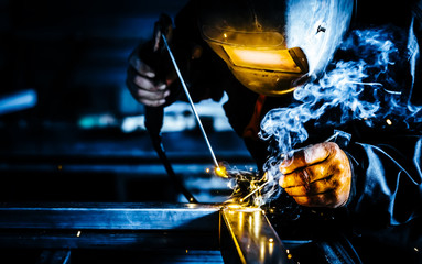 Professional mask protected welder man working on metal welding and sparks metal.