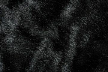 Highly detailed background texture of black fur made of synthetic animal long hair.