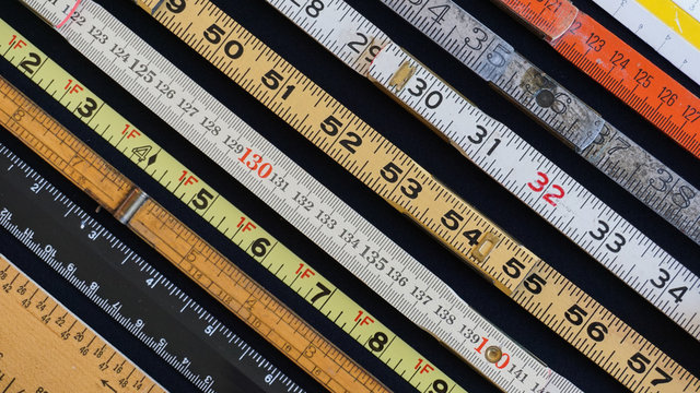 Rulers and scales in metric and inch measurement represent concepts of metrics, precision, accuracy and results.