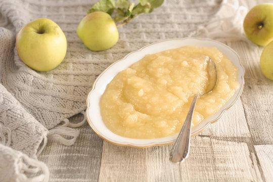 Selbst gekochter frischer Apfelmus in einer Porzellanschale mit frischen Äpfeln als Dekoration