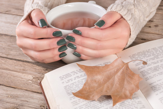Woman hands in sweater with olive color manicure holds cup of tea and open book with dry fallen leaf on retro wooden desk. Autumn concept. Close up, selective focus