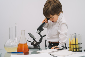 The boy with a microscope and various colorful flasks on a white background. A boy doing experiments in the laboratory. Explosion in the laboratory. Science and education.