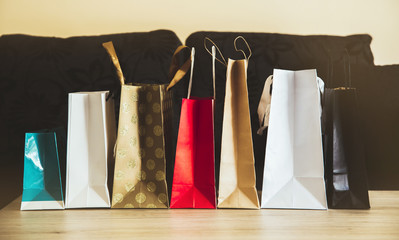 Different color and size paper shopping bags in a row on living room table, dark couch background. Christmas or just shopping concept.