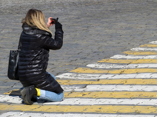 Girl in black down jacket taking pics on mobile camera. Kneeling woman with a smartphone photographing on pedestrian crossing