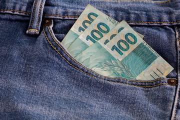 Real hundred brazilian money notes in pocket jeans. 100. Brazil finance.