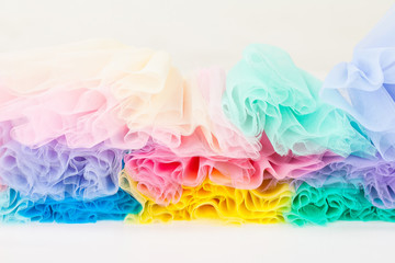 Pieces of colored corrugated tulle fabric, stacked on top of each other. end view