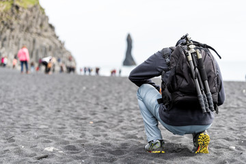 Myrdal, Iceland Reynisfjara black sand beach from volcanic rocks, formation, seashore, shore, coastline, many people, tourists walking, man backpack photographer, tripod, basalt columns