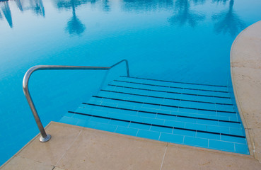 Swimming pool stairs in two tones of blue color with trees reflection on the water, top view