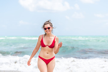 Young happy smiling woman walking front in red swimsuit bikini bathing suit, sunglasses looking straight by wave on Sunny Isles, Miami Beach in Florida, water, seaweed