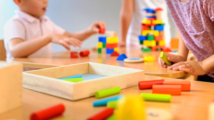 Children playing with colorful wooden didactic toys at kindergarten