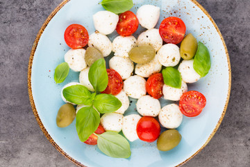 Delicious caprese salad with ripe cherry tomatoes and mini mozzarella cheese balls with fresh basil leaves.