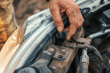 Auto mechanic holds electric cable in hand and repairing headlight or headlamp of car