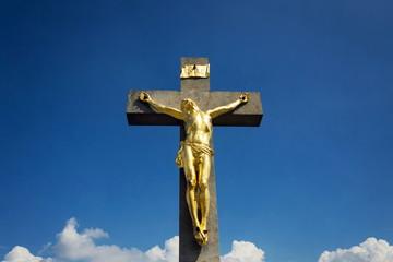 Golden Jesus Christ crucifixion statue, sunny summer day blue sky background, Vrbice, Moravia, Czech Republic