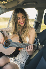 Happy woman playing guitar while sitting in car