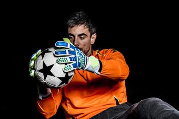 Goalie holding soccer ball while sitting against black background
