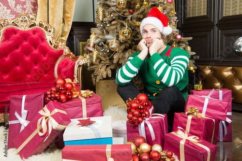 eeebf728f4582 Man with present boxes at christmas tree. Man prepare present packs on new  year eve. Man in santa costume celebrate new year. Santa stops here