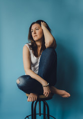 Thoughtful woman looking away while sitting on stool against blue background