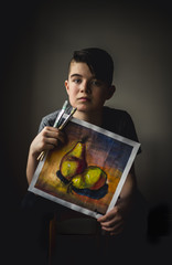 Portrait of boy holding painting while sitting against wall at home