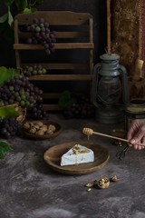 Brie cheese on a wooden plate. With grapes, nuts and honey
