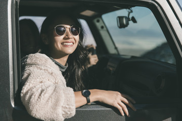 Cheerful young woman wearing sunglasses while sitting in off-road vehicle at desert during sunny day
