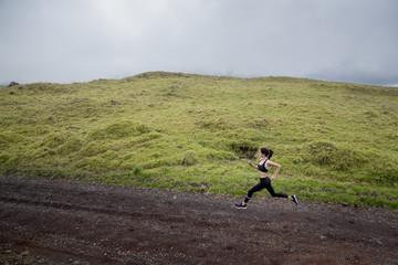Woman jogging along dirt road, Kailua Kona, Hawaii, USA