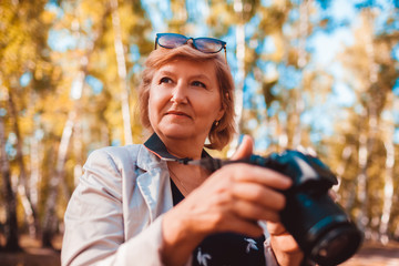 Middle-aged woman checking images on camera in autumn forest. Senior woman walking and enjoying hobby