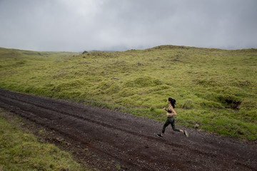Woman jogging on dirt road amidst green landscape against cloudy sky